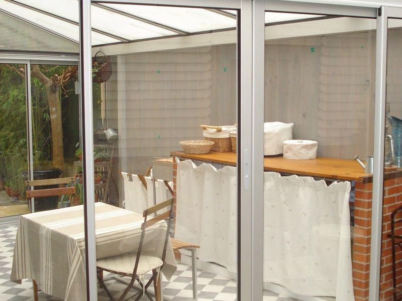 2009,Cagne 06,création et pose d'une véranda en appui sur un mur mitoyen,toiture en polycarbonate,fenêtres coulissantes quatre et trois vantaux,teinte gris argent,store toile protégeant du soleil.