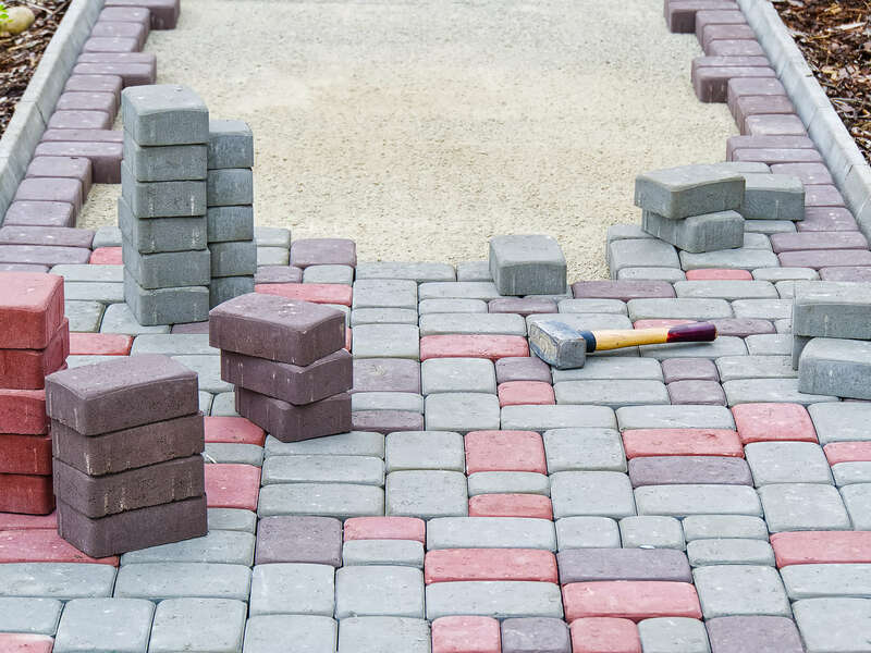 worker-laying-paving-stones-stone-pavement-construction-worker-laying-cobblestone-rocks-sand