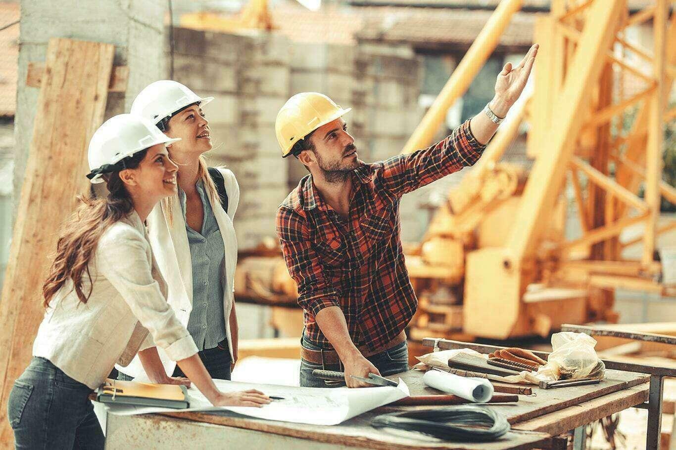 trois constructeurs pointant le haut du projet, du doigt