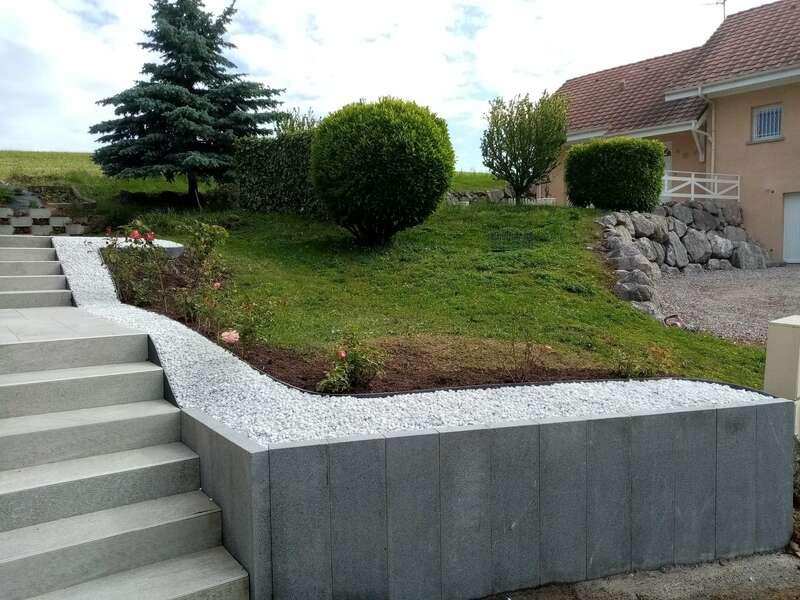 Muret en blocs de granit et contour en gravier blanc / béton lavé
