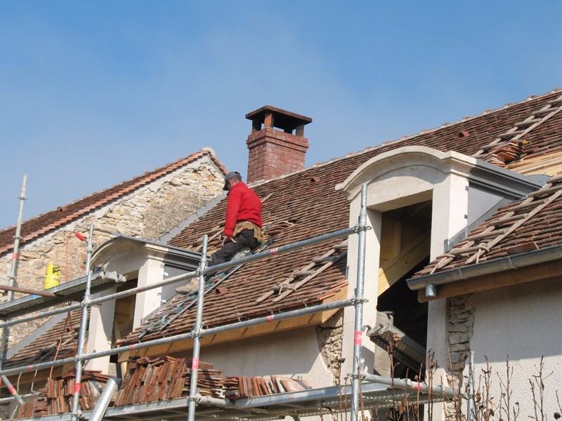 Travaux de zinguerie sur des lucarnes en pierre avec toit cintré.