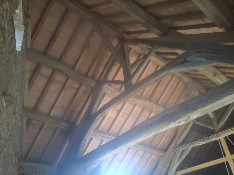 Vue de dessous de la charpente de l'écurie en vieux bois de chêne et douglas.