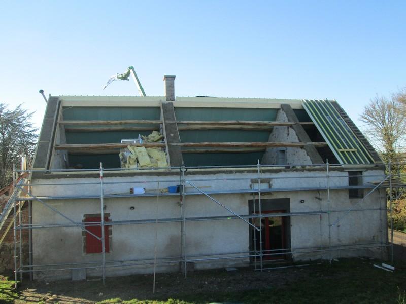 Restauration d'une maison ancienne avec pannes en chêne conservées et redressées.