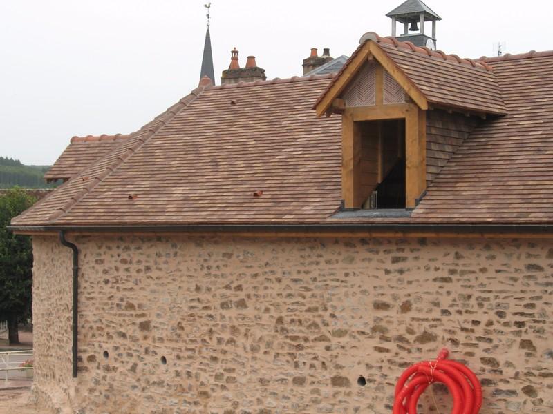 Lucarne à chevalet lasurée, habillée en brique et tuile plate.