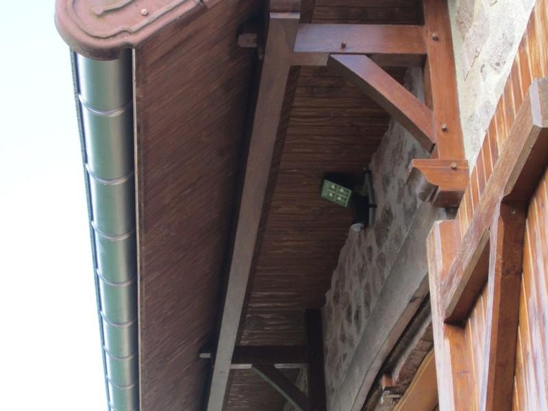 Prolongement d'un pan de toiture de 1 mètre avec consoles et sablière en chêne.