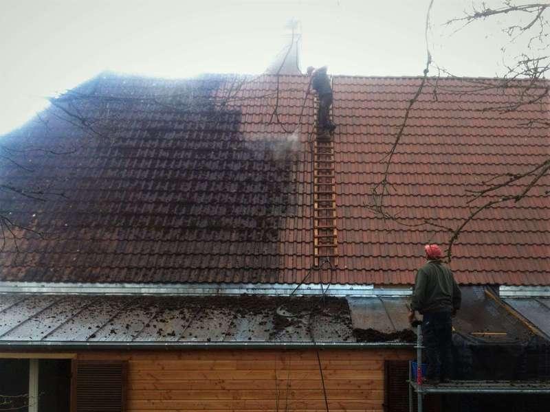 Démoussage d'un toit en tuile béton.