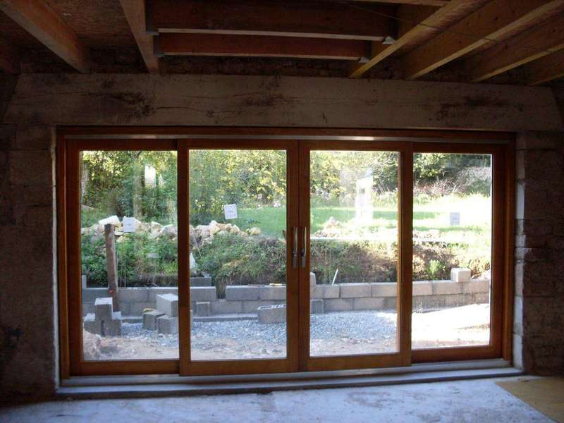 Baie vitrée en bois, lazurée par le client (Mélèze) Vue intérieure de cette belle menuiserie de 4 mètres de large. Elle est construite en lamellé collé afin de garantir une bonne stabilité dans de temps.